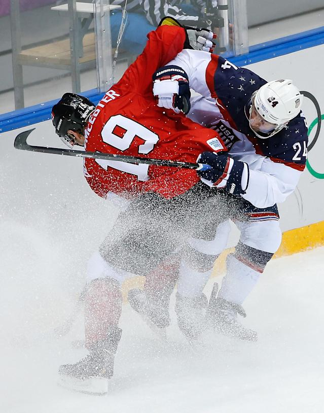 Canada defenseman Jay Bouwmeester and USA forward Ryan Callahan collide during the first period of the men's semifinal ice hockey game at the 2014 Winter Olympics, Friday, Feb. 21, 2014, in Sochi, Russia. (AP Photo/Matt Slocum)