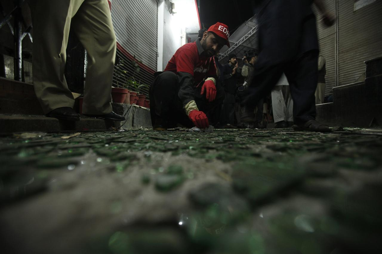 A rescue worker collects evidence at the site of a bomb blast in Peshawar February 4, 2014. A suicide bomber killed at least eight people on Tuesday near a mosque frequented by minority Shi'ite worshippers in a densely populated neighbourhood of the Pakistani city of Peshawar, police and doctors said. Najeeb Rehman, a senior policeman, said the attack, possibly the work of more than one suicide bomber, had taken place as worshippers left the mosque and walked towards a local hotel. REUTERS/Fayaz Aziz (PAKISTAN - Tags: POLITICS CIVIL UNREST CRIME LAW)