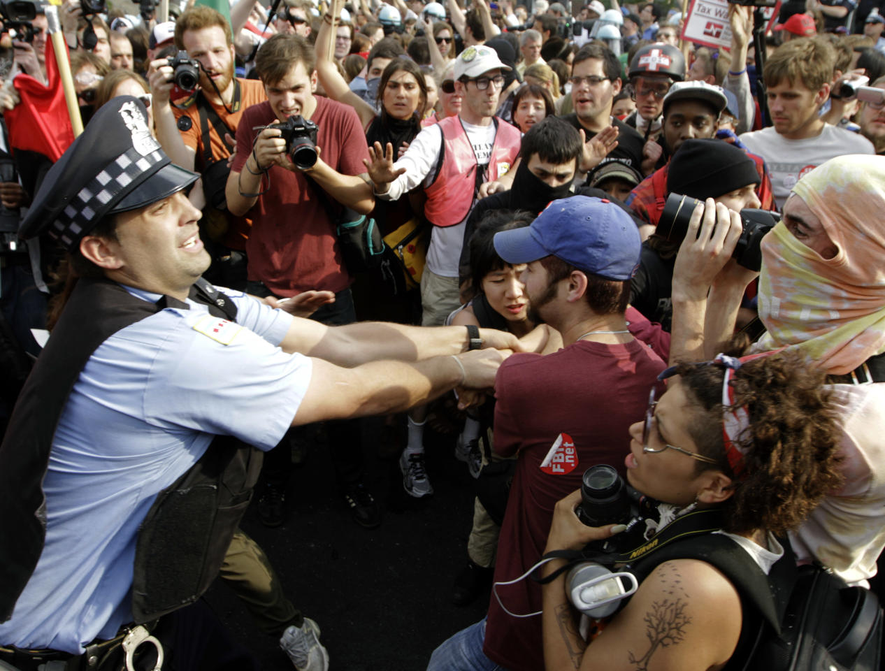 Demonstrators make a futile attempt to stop a Chicago police officer from detaining a protester during this weekend's NATO summit in Chicago Sunday, May 20, 2012 in Chicago. (AP Photo/Seth Perlman)