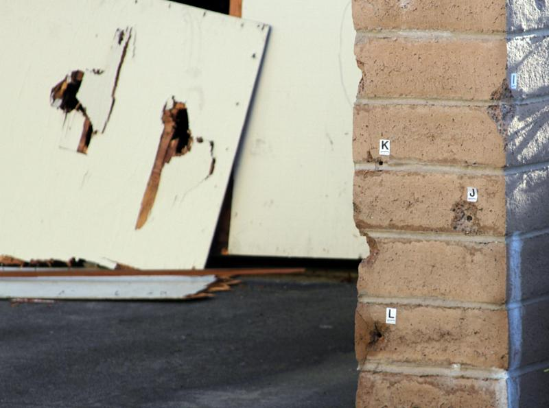A bullet riddled garage door and wall is seen in Santa Cruz, Calif., on Wednesday, Feb. 27, 2013 where a suspected murderer was shot Tuesday afternoon after he allegedly killed two Santa Cruz Police Department detectives.  Sgt. Loran Butch Baker and Detective Elizabeth Butler were shot and killed outside the home of coffee shop worker Jeremy Goulet, 35, who was suspected of making inappropriate sexual advances toward a co-worker at her home, authorities said. The shootout occurred about 60 miles south of San Francisco.  Goulet died in the shootout with police. (AP Photo/Thomas Mendoza)