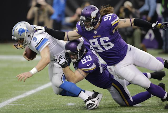 Detroit Lions quarterback Matthew Stafford, left, is sacked by Minnesota Vikings defenders Jared Allen (69) and Brian Robison (96) during the first half of an NFL football game, Sunday, Dec. 29, 2013, in Minneapolis. (AP Photo/Ann Heisenfelt)
