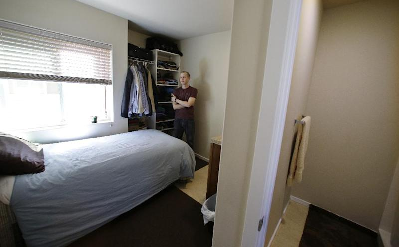 In this photo taken Wednesday, April 24, 2013, Kris King spreads stands in his tiny apartment in Seattle. Even King was initially shocked by the size of the apartment he rented near downtown, roughly the size of large parking spot. Cities such as San Francisco, New York and Boston have been encouraging tiny apartments to cater to young workers, retirees others who prefer city dwelling, singles or students. San Francisco last fall approved construction of apartments as small as 220 square feet, while Boston has approved 300 new units as small as 375 sq. feet. But in Seattle, where city codes have allowed for even smaller micro-apartments and dozens have been built in the last five years, the trend is facing a backlash from some neighbors who are pushing for a building moratorium or for them to be more adequately regulated. (AP Photo/Elaine Thompson)