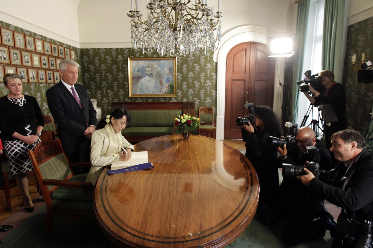 Myanmar opposition leader Aung San Suu Kyi, third from left, signs a book at the Nobel Institute after a meeting with the Norwegian Nobel Committee members in Oslo, Norway, Saturday, June 16, 2012. It's been 21 years, and Suu Kyi is about to give her Nobel Peace Prize acceptance speech. (AP Photo/Cathal McNaughton, Pool)