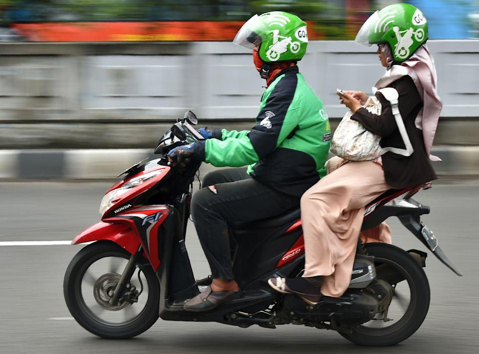 CORRECTION - A Gojek rider transports a passenger in Jakarta on February 2, 2017. / AFP / Bay ISMOYO / The erroneous mention[s] appearing in the metadata of this photo by Bay ISMOYO has been modified in AFP systems in the following manner: [Gojek] instead of [GrabBike], and [removes second sentence]. Please immediately remove the erroneous mention[s] from all your online services and delete it (them) from your servers. If you have been authorized by AFP to distribute it (them) to third parties, please ensure that the same actions are carried out by them. Failure to promptly comply with these instructions will entail liability on your part for any continued or post notification usage. Therefore we thank you very much for all your attention and prompt action. We are sorry for the inconvenience this notification may cause and remain at your disposal for any further information you may require. (Photo credit should read BAY ISMOYO/AFP/Getty Images)
