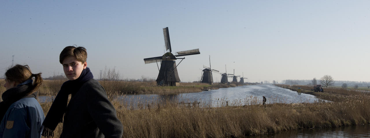 FILE - In this Feb. 14, 2017, file photo, tourists walk by windmills lining Hooge Boezem van de Overwaard canal at the Unesco World Heritage site in Kinderdijk, Netherlands. (AP Photo/Peter Dejong, File)