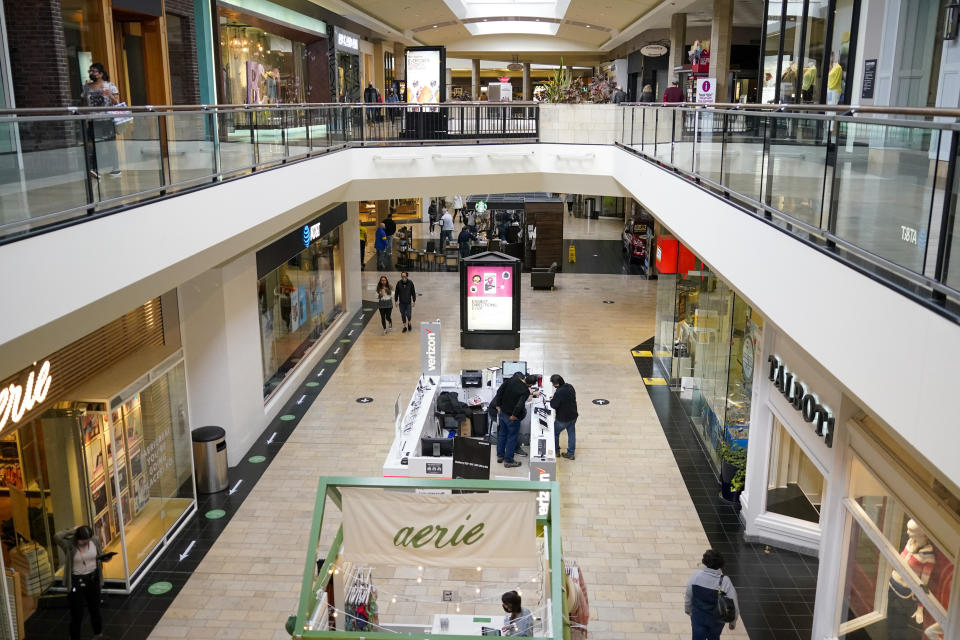 In this photo made on Wednesday, Feb. 24, 2021, people walks through a shopping mall in Pittsburgh. (AP Photo/Keith Srakocic)