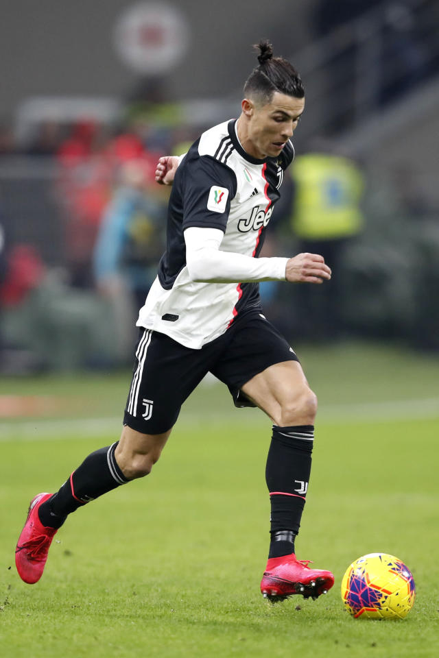 Juventus' Cristiano Ronaldo runs with the ball during an Italian Cup soccer match between AC Milan and Juventus at the San Siro stadium, in Milan, Italy, Thursday, Feb. 13, 2020. (AP Photo/Antonio Calanni)