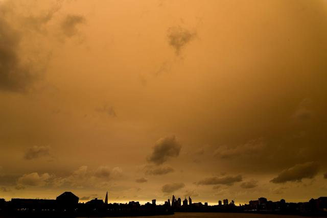 <p>Darkened sky over London is pictured at financial district of Canary Wharf, London on October 16, 2017. The darkening is caused by warm air and dust swept up by storm Ophelia. The sun shone red and the sky darkened to a foreboding orange and brown across parts of Britain (Photo: Alberto Pezzali/NurPhoto via Getty Images) </p>