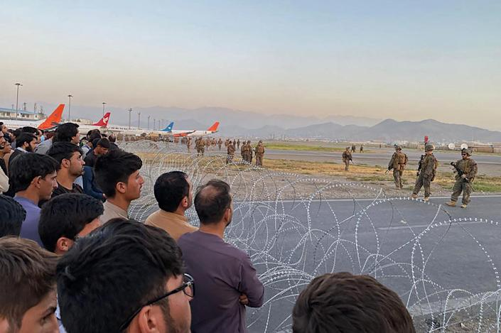 Afghans (L) crowd at the airport as US soldiers stand guard in Kabul on August 16, 2021. (Shakib RahmaniAFP via Getty Images)