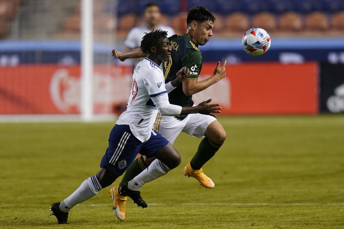 Portland Timbers forward Felipe Mora, right, and Vancouver Whitecaps midfielder Janio Bikel, left, battle for the ball in the first half during an MLS soccer game Sunday, April 18, 2021, in Sandy, Utah. (AP Photo/Rick Bowmer)