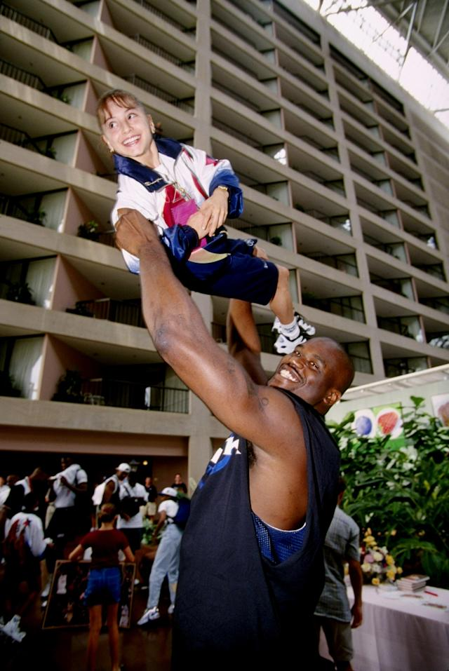 Shaquille O'Neal of the Dream Team lifts up Dominique Moceanu of the USA gymnastics team at the 1996 Centennial Olympic Games in Atlanta, Georgia.