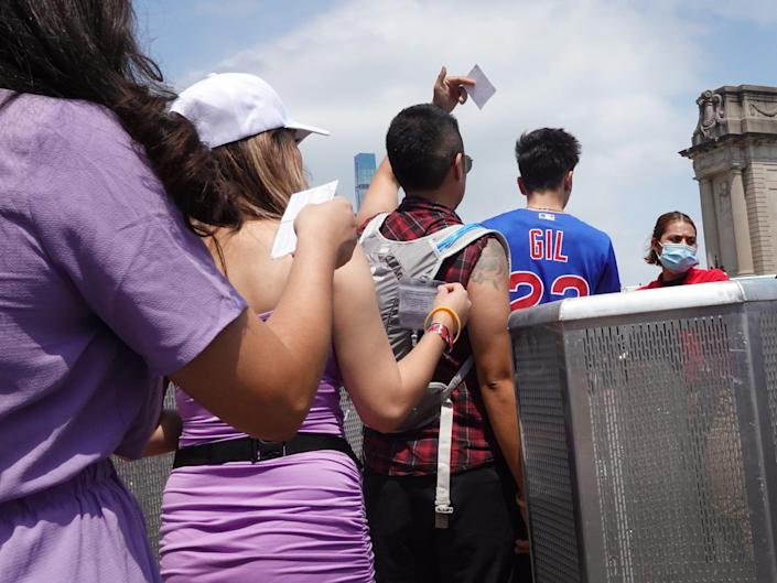 Festival goers stand in line to show their COVID-19 vaccination cards to Lollapalooza staff.
