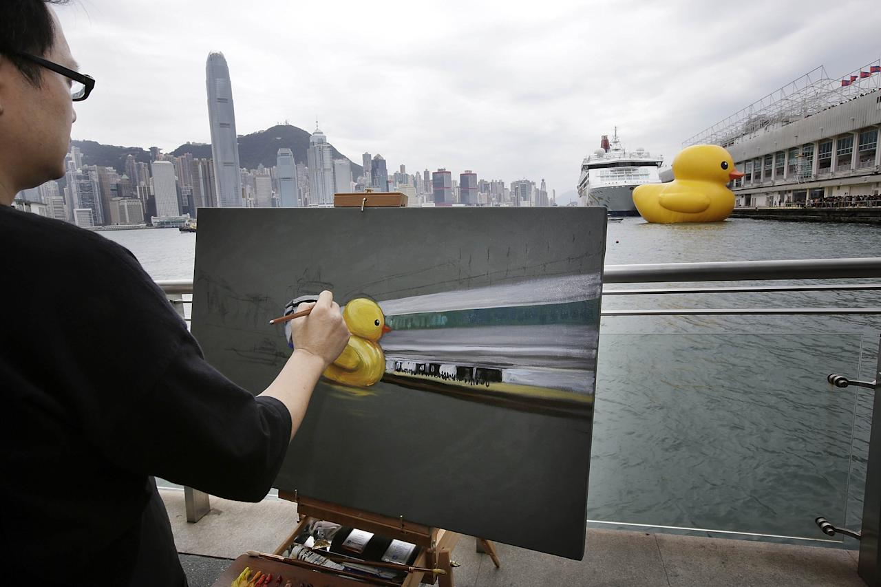 """HONG KONG - MAY 02: A man paints Dutch conceptual artist, Florentijin Hofman's Floating duck sculpture called """"Spreading Joy Around the World"""" as it arrives in Victoria Harbour on May 2, 2013 in Hong Kong. The """"Rubber Duck"""", which is 16.5 meters high, will be in Hong Kong from May 2 to June 9. Since 2007, """"Rubber Duck"""" has been traveling to 10 countries and 12 cities. (Photo by Jessica Hromas/Getty Images)"""