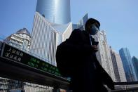 FILE PHOTO: Pedestrian wearing a face mask walks near an overpass with an electronic board showing stock information in Shanghai