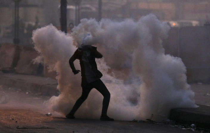 An anti-government protester is surrounded by tear gas fired by Iraqi security forces in an effort to disperse demonstrators, in central Baghdad, Iraq, Sunday, Nov. 10, 2019. (AP Photo/Hadi Mizban)