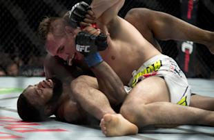 Rory MacDonald pins down Tyron Woodley during their welterweight title fight. (AP)