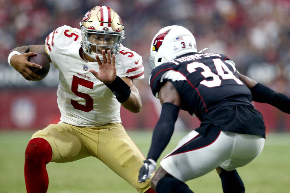 San Francisco 49ers quarterback Trey Lance (5) tries to elude Arizona Cardinals free safety Jalen Thompson (34) during the second half of an NFL football game, Sunday, Oct. 10, 2021, in Glendale, Ariz. (AP Photo/Ralph Freso)