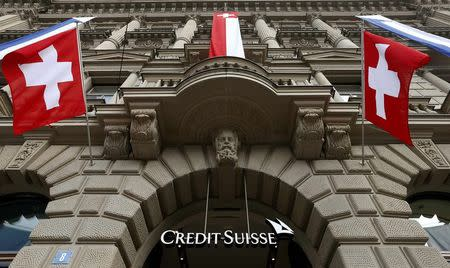 National flags of Switzerland fly over the entrance of the headquarters of Swiss bank Credit Suisse in Zurich