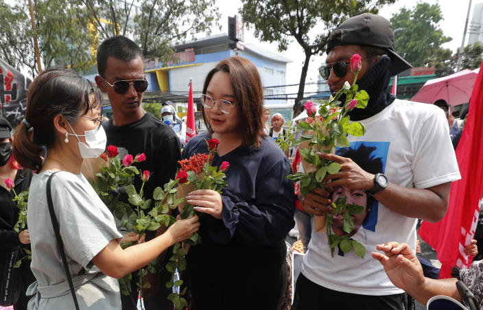 Pro-democracy activists, from second left, Panupong Jadnok, Panusaya Sithijirawattanakul and Jatupat Boonpattararaksa receive a flower from a supporter as they arrived at the Attorney General office in Bangkok, Thailand, Monday, March 8, 2021. Prosecutors in Thailand charged 18 pro-democracy activists with sedition on Monday, while lodging additional charges of insulting the monarchy against three of them. (AP Photo/Sakchai Lalit)