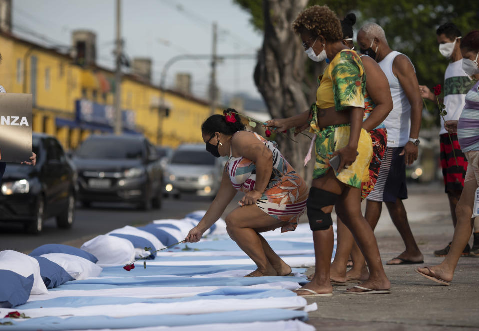 Residents place roses on mattresses symbolizing COVID-19 victims, during a protest against the Government's handling of the COVID-19 pandemic, organized by the Rio de Paz NGO, in front of the Ronaldo Gazolla hospital in Rio de Janeiro, Brazil, Wednesday, March 24, 2021. (AP Photo/Silvia Izquierdo)