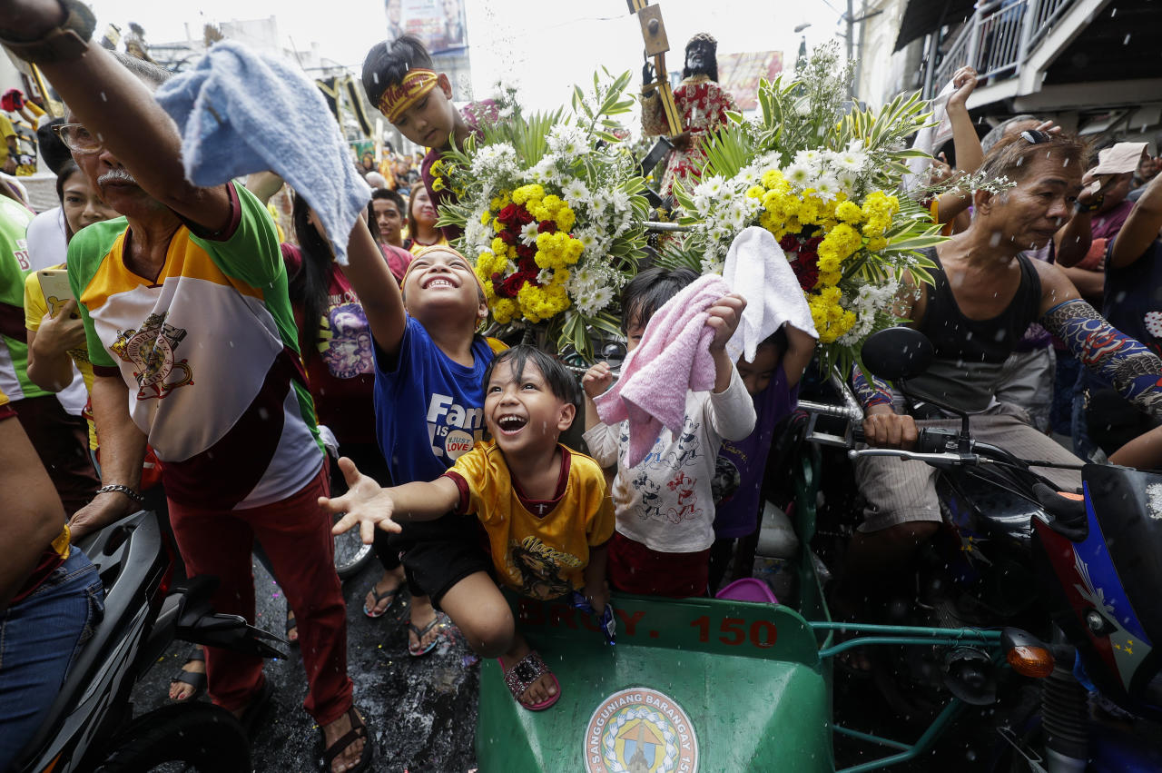 Young devotees react during the traditional blessing of religious statues ahead of the celebration of the Feast of the Black Nazarene on Tuesday Jan. 7, 2020 in Manila, Philippines. Tens of thousands of Roman Catholic devotees are expected to join the long and raucous procession around Manila streets to celebrate the Feast Day of the Black Nazarene on Jan. 9. (AP Photo/Aaron Favila)