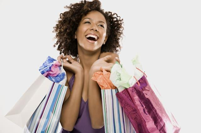 Young woman carrying shopping bags over shoulder, smiling, close-up