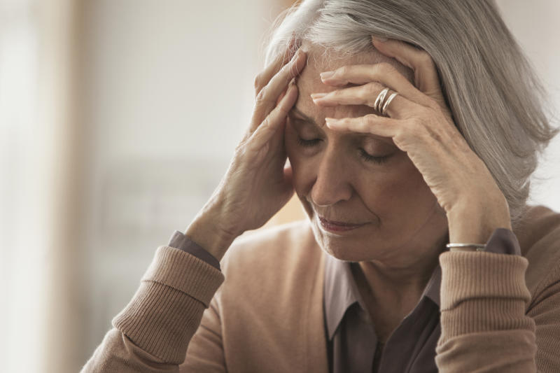 Senior Caucasian woman holding her forehead