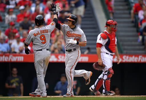 Baltimore Orioles' Manny Machado, center, is congratulated by Nate McLouth after hitting a two-run home run as Los Angeles Angels catcher Chris Iannetta looks on during the fifth inning of their baseball game on Sunday, May 5, 2013, in Anaheim, Calif. (AP Photo/Mark J. Terrill)