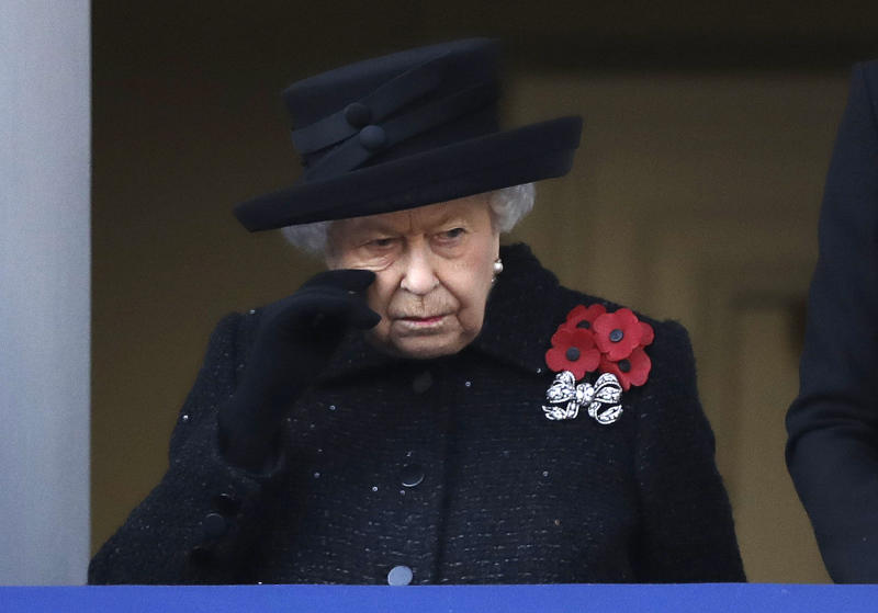 Britain's Queen Elizabeth II wipes her cheek as she watches the Remembrance Sunday ceremony at the Cenotaph in Whitehall in London, Sunday, Nov. 10, 2019. Remembrance Sunday is held each year to commemorate the service men and women who fought in past military conflicts. (AP Photo/Matt Dunham)