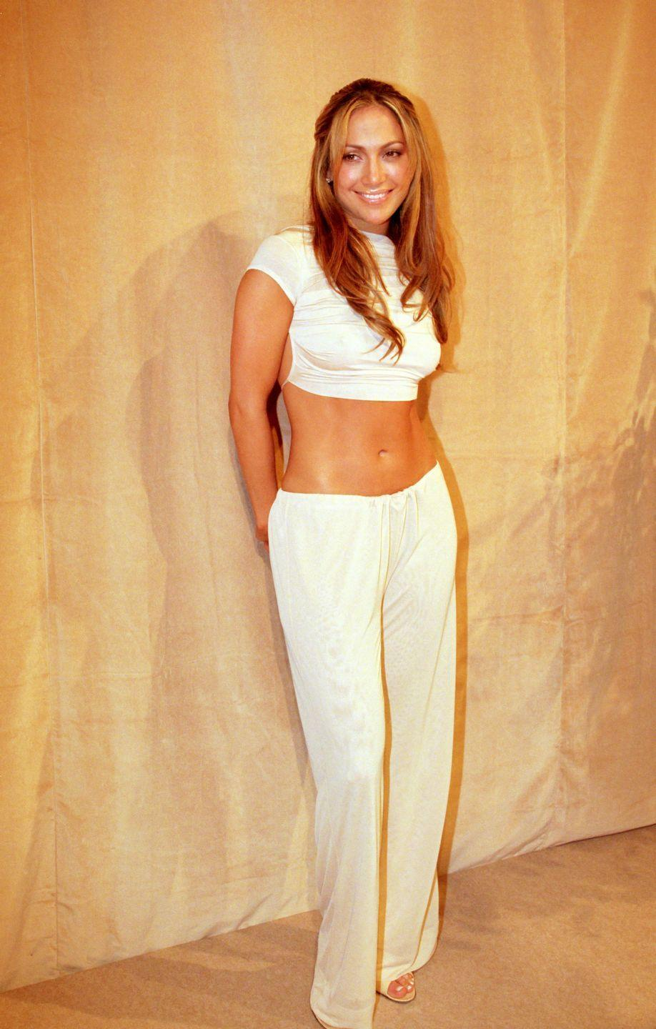 <p>A classic nineties look of low-slung trousers and a crop top, in white. </p>