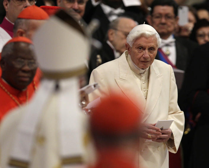 Pope Emeritus Benedict XVI looks at Pope Francis, left with back to camera, arriving as he attends a consistory inside the St. Peter's Basilica at the Vatican, Saturday, Feb.22, 2014. Benedict XVI has joined Pope Francis in a ceremony creating the cardinals who will elect their successor in an unprecedented blending of papacies past, present and future. (AP Photo/Alessandra Tarantino)
