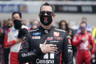 Kyle Busch puts his hand over his heart during the national anthem prior to the start of the NASCAR Truck Series auto race at Richmond International Raceway in Richmond, Va., Saturday, April 17, 2021. (AP Photo/Steve Helber)