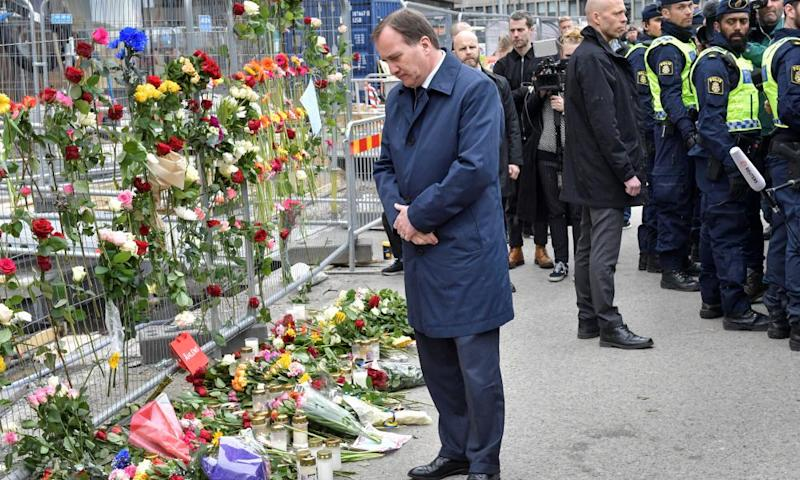 Swedish prime minister Stefan Löfven looks at flowers as he visits the crime scene in central Stockholm.