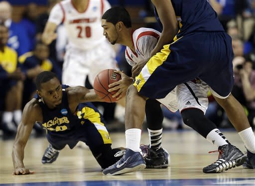 North Carolina A&T guard Lamont Middleton (30) tries to steal the ball from Louisville guard Peyton Siva (3) during the first half of their second-round NCAA college basketball tournament game, Thursday, March 21, 2013, in Lexington, Ky. (AP Photo/John Bazemore)