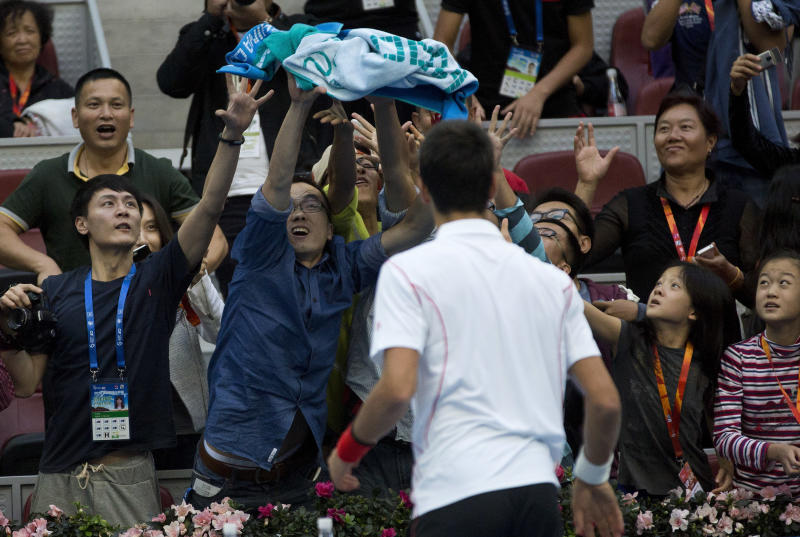 Spectators try to grab a towel thrown by Novak Djokovic of Serbia after he defeated Lukas Rosol of the Czech Republic in the China Open tennis tournament at the National Tennis Stadium in Beijing, China Tuesday, Oct. 1, 2013. (AP Photo/Andy Wong)