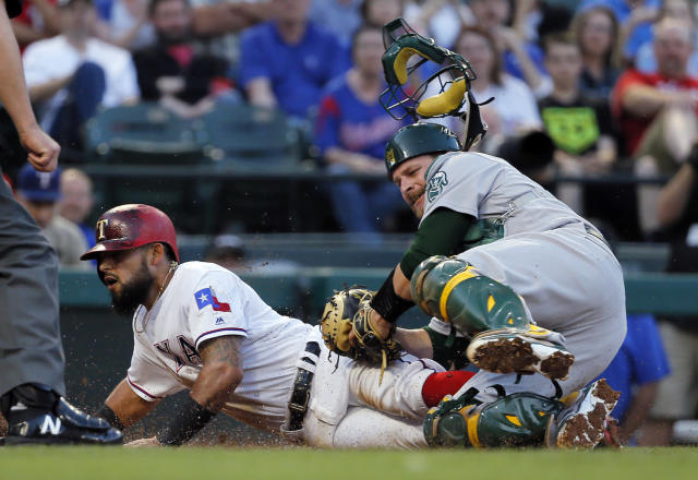 <p>Texas Rangers' Rougned Odor, left, is tagged out at home by Oakland Athletics catcher Stephen Vogt as Odor was trying to score on a ball hit by Carlos Gomez during the second inning of a baseball game, May 12, 2017, in Arlington, Texas. (Photo: Tony Gutierrez/AP) </p>