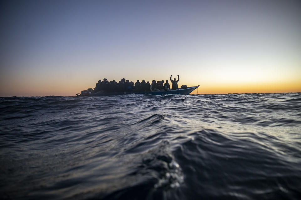 Migrants and refugees from different African nationalities wait for assistance aboard an overcrowded wooden boat, as aid workers of the Spanish NGO Open Arms approach them in the Mediterranean Sea, international waters, at 122 miles off the Libyan coast, Friday, Feb. 12, 2021. Various African migrants drifting in the Mediterranean Sea after fleeing Libya on unseaworthy boats have been rescued. In recent days, the Libyans had already thwarted eight rescue attempts by the Open Arms, a Spanish NGO vessel, harassing and threatening its crew in international waters. (AP Photo/Bruno Thevenin)