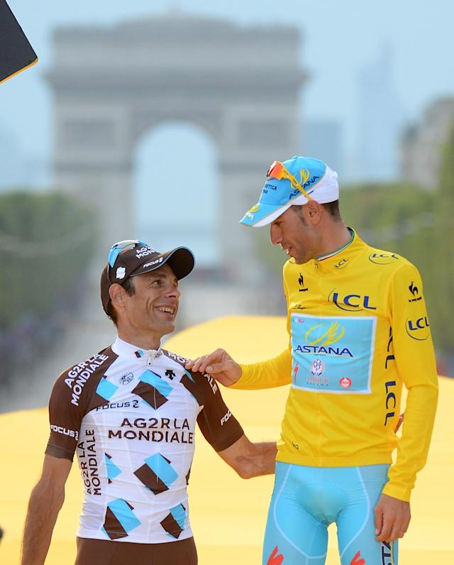 Race winner Vincenzo Nibali of Italy, wearing the overall leader's yellow jersey, chats witi second placed Jean-Christophe Peraud of France on the podium of the Tour de France in Paris, France, Sunday, July 27, 2014. (AP Photo/Jerome Prevost, Pool)