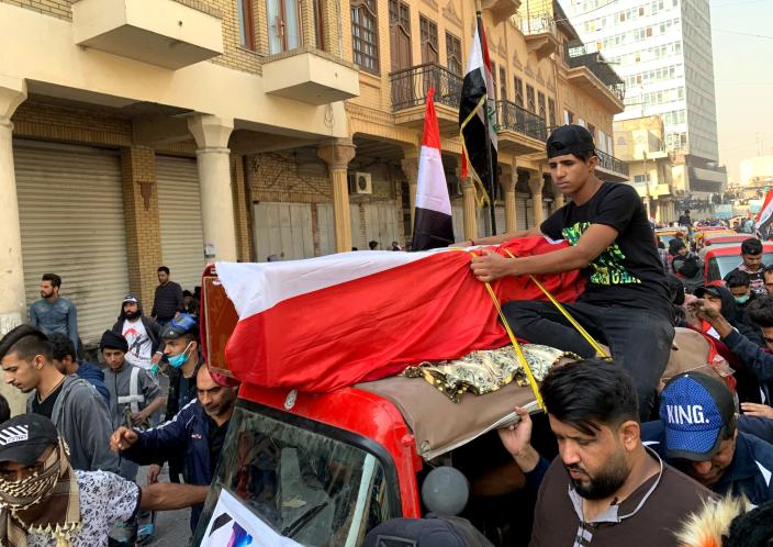 Mourners and protesters escort the flag-draped coffin of Munir Ali, whose family said was killed in anti-government demonstrations, during his funeral in Baghdad, Iraq, Sunday, Nov. 24, 2019. (AP Photo/Ali Abdul Hassan)