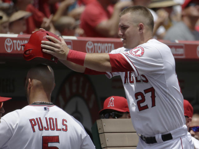 Los Angeles Angels' Albert Pujols, left, celebrates with Mike Trout after scoring on a hit by Erick Aybar against the Minnesota Twins during the first inning of a baseball game in Anaheim, Calif., Thursday, June 26, 2014. (AP Photo/Chris Carlson)