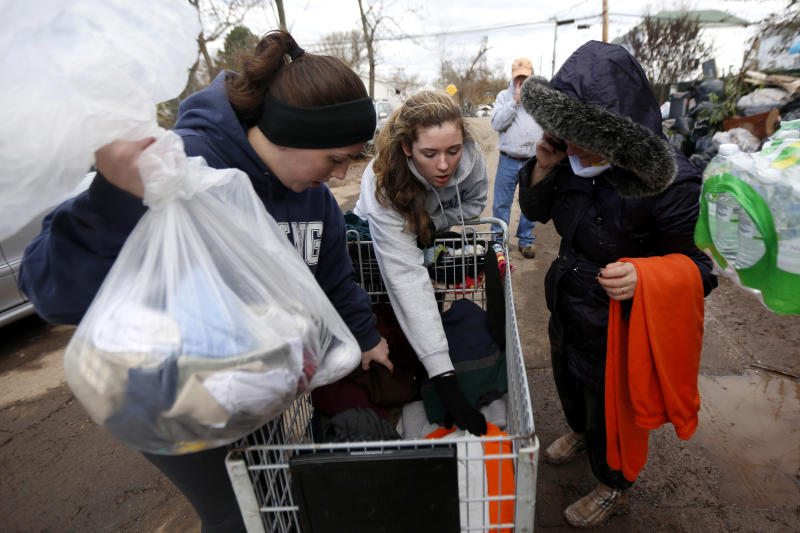 Volunteers Laurie McLoughlin, left, and her sister Caitlin McLaughlin, center, sort through clothing to donate to a resident, Saturday, Nov. 3, 2012, in Staten Island, N.Y.  A Superstorm Sandy relief fund is being created just for residents of the hard-hit New York City borough. Former Mayor Rudolph Giuliani and Borough President James Molinaro say the fund will help residents displaced from their homes. (AP Photo/Julio Cortez)