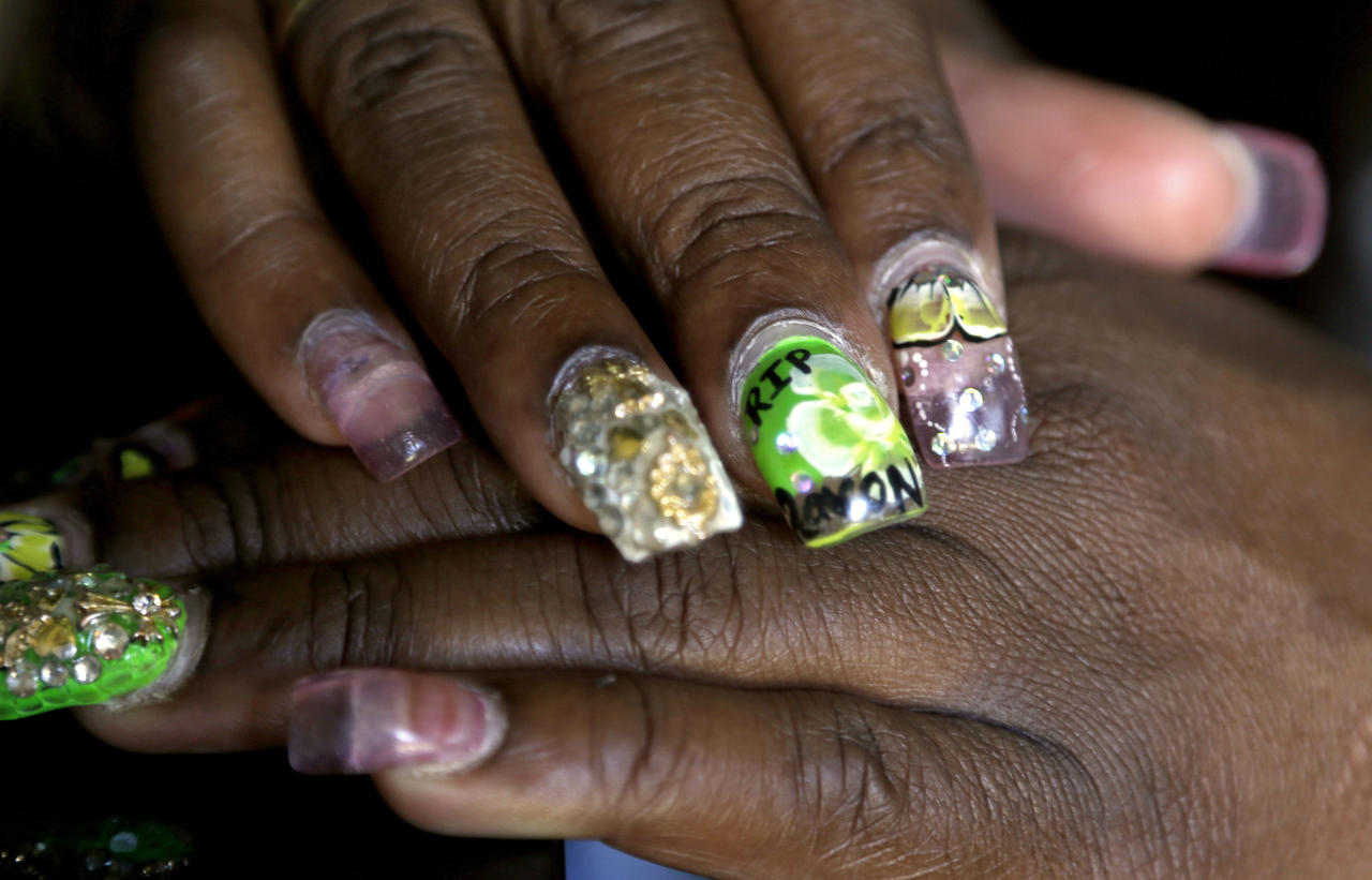 "In this July 8, 2014 photo, Felicia Jordan rests her hands with decorative fingernails, inspired by her deceased 19-year-old son Ravon who died after being shot in a gang crossfire, in Fayetteville, N.C. Ravon spoke out against gun violence at a city council meeting after his best friend, Shaniqua Simmons, and her boyfriend were gunned down in an apartment at the former Cambridge Arms. ""I don't feel like, as a resident in an apartment complex, you should be paying basically for your grave site,"" Ravon said. ""You shouldn't be paying to be killed or murdered in your own house."" (AP Photo/Gerry Broome)"