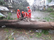 This photograph provided by India's National Disaster Response Force (NDRF) shows NDRF personnel a tree that feel down amid heavy rain and winds at Mahuva town in Bhavnagar District, in Gujarat state, India, Tuesday, May 18, 2021. Cyclone Tauktae that emerged in the Arabian Sea made landfall on India's western coast on Monday, hours after authorities evacuated hundreds of thousands of people and suspended COVID-19 vaccinations in one state. (National Disaster Response Force via AP)
