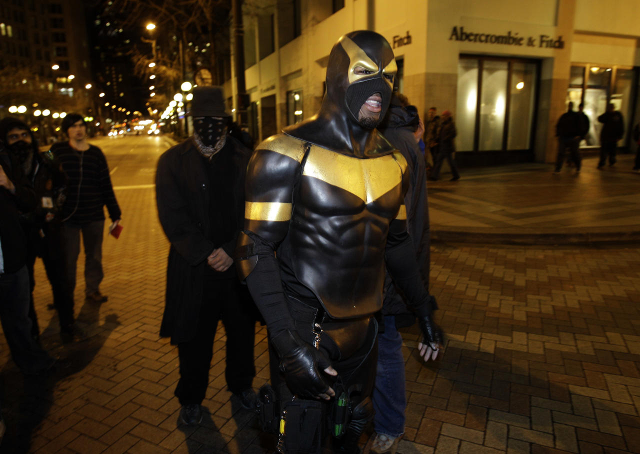 "This Feb. 16, 2011 photo shows self-styled Seattle superhero ""Phoenix Jones,"" center, in downtown Seattle. Police officers arrested Phoenix Jones early Sunday, Oct. 9, 2011, after he was accused of assaulting several people with pepper spray. (AP Photo/Ted S. Warren)"