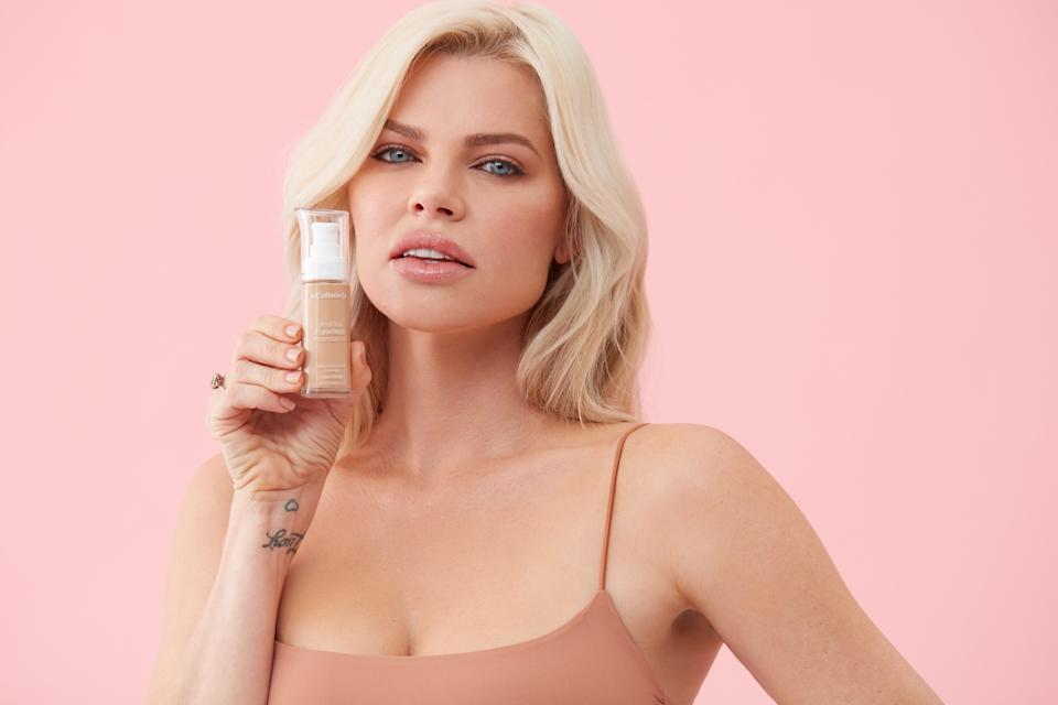 Sophie Monk poses with a bottle of MCoBeauty foundation in a promotional image