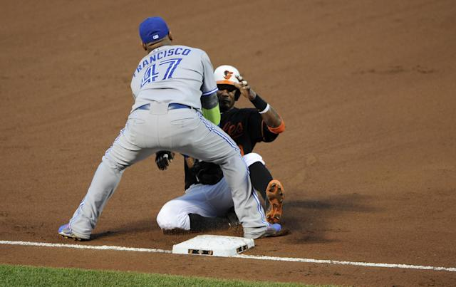 Baltimore Orioles' Adam Jones, right, is out at third by Toronto Blue Jays third baseman Juan Francisco (47) on a ground ball hit by Nelson Cruz during the fourth inning of a baseball game on Friday, June 13, 2014, in Baltimore. (AP Photo/Nick Wass)