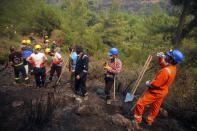 Turkish volunteers work as they fight wildfires in Turgut village, near tourist resort of Marmaris, Mugla, Turkey, Wednesday, Aug. 4, 2021. As Turkish fire crews pressed ahead Tuesday with their weeklong battle against blazes tearing through forests and villages on the country's southern coast, President Recep Tayyip Erdogan's government faced increased criticism over its apparent poor response and inadequate preparedness for large-scale wildfires.(AP Photo/Emre Tazegul)
