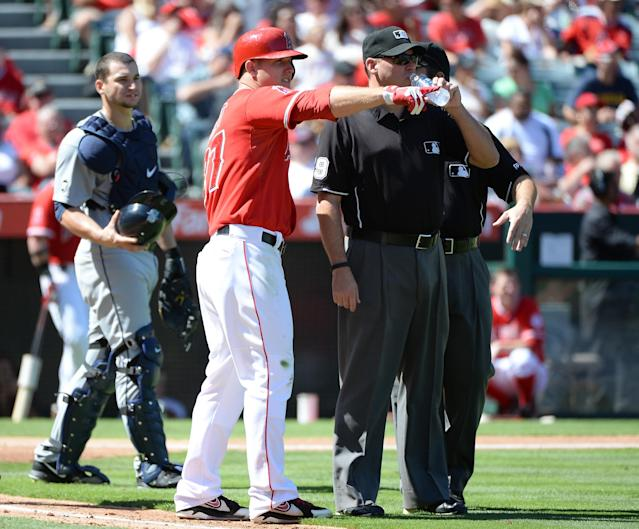 ANAHEIM, CA - SEPTEMBER 22: Mike Trout #27 of the Los Angeles Angels points out bees to umpires and Mike Zunino #3 of the Seattle Mariners during a delay in the third inning at Angel Stadium of Anaheim on September 22, 2013 in Anaheim, California. (Photo by Harry How/Getty Images)