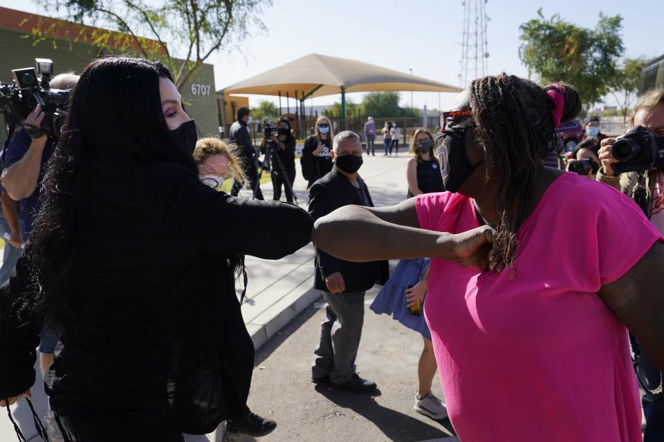 Iconic singer Cher, left, gives an elbow bump to Berdetta Hodge, right, of Tempe, Ariz., at a polling station as she campaigns for Democratic presidential candidate Joe Biden, Monday, Oct. 26, 2020, in Phoenix. (AP Photo/Ross D. Franklin)