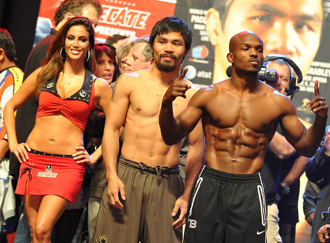 Manny Pacquiao (C) of the philippines and Timothy Bradley of US (R) attend weigh-in session at the MGM Grand Arena in Las Vegas, Nevada on June 08, 2012.  Pacquiao and Bradley will fight on June 9.      AFP PHOTO / JOE KLAMARJOE KLAMAR/AFP/GettyImages
